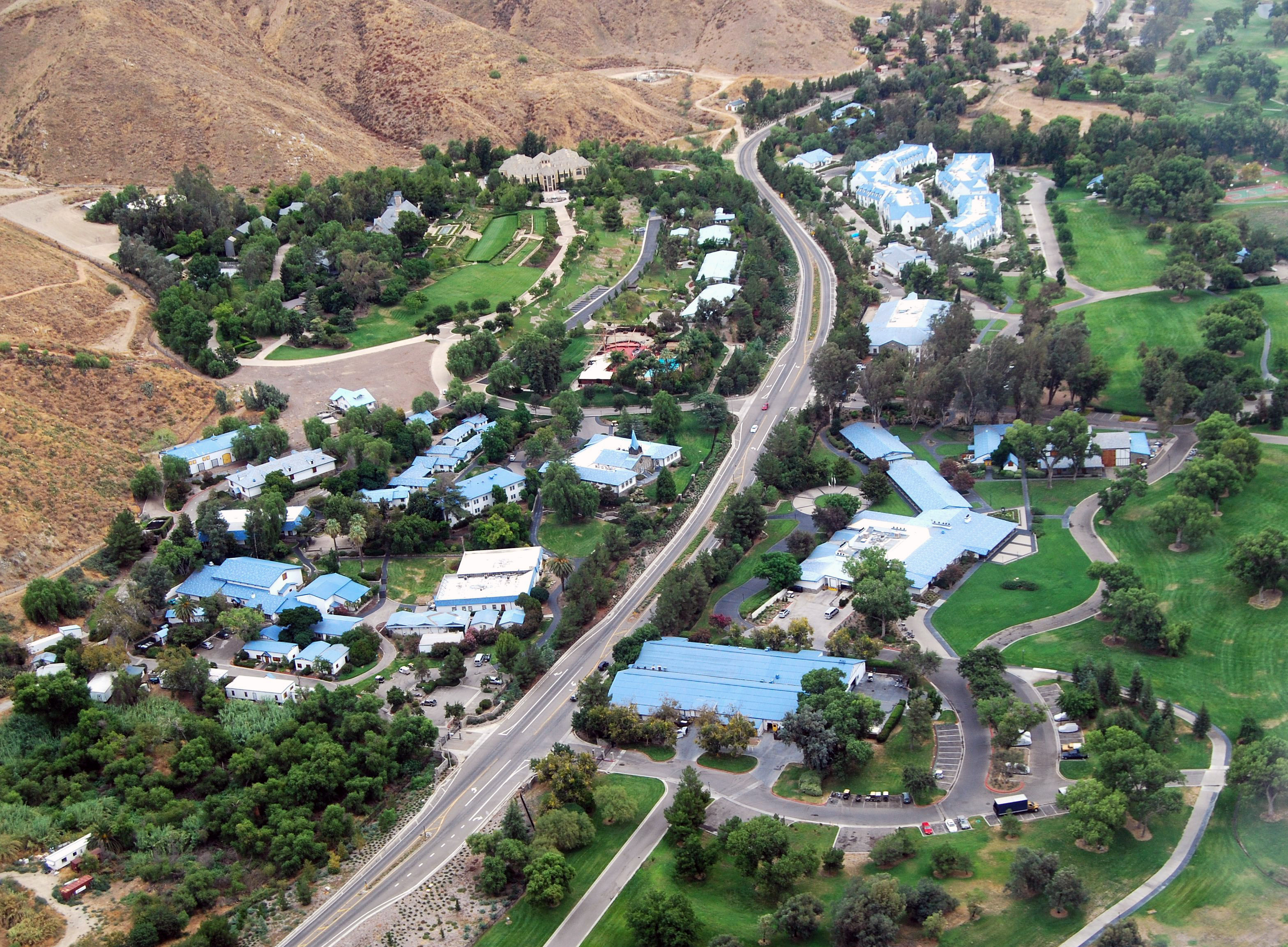Aerial view of Gold Base from the west, showing the garage in the foreground, with Massacre Canyon Inn behind and the Staff Berthing buildings beyond, to the right of the highway. The buildings in the foreground on the left of the highway are mostly us
