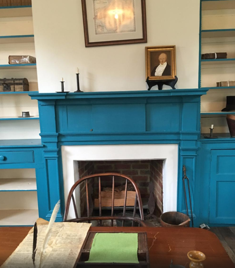 A closeup of a writing desk and fireplace in the Badger Iredell Law Office.