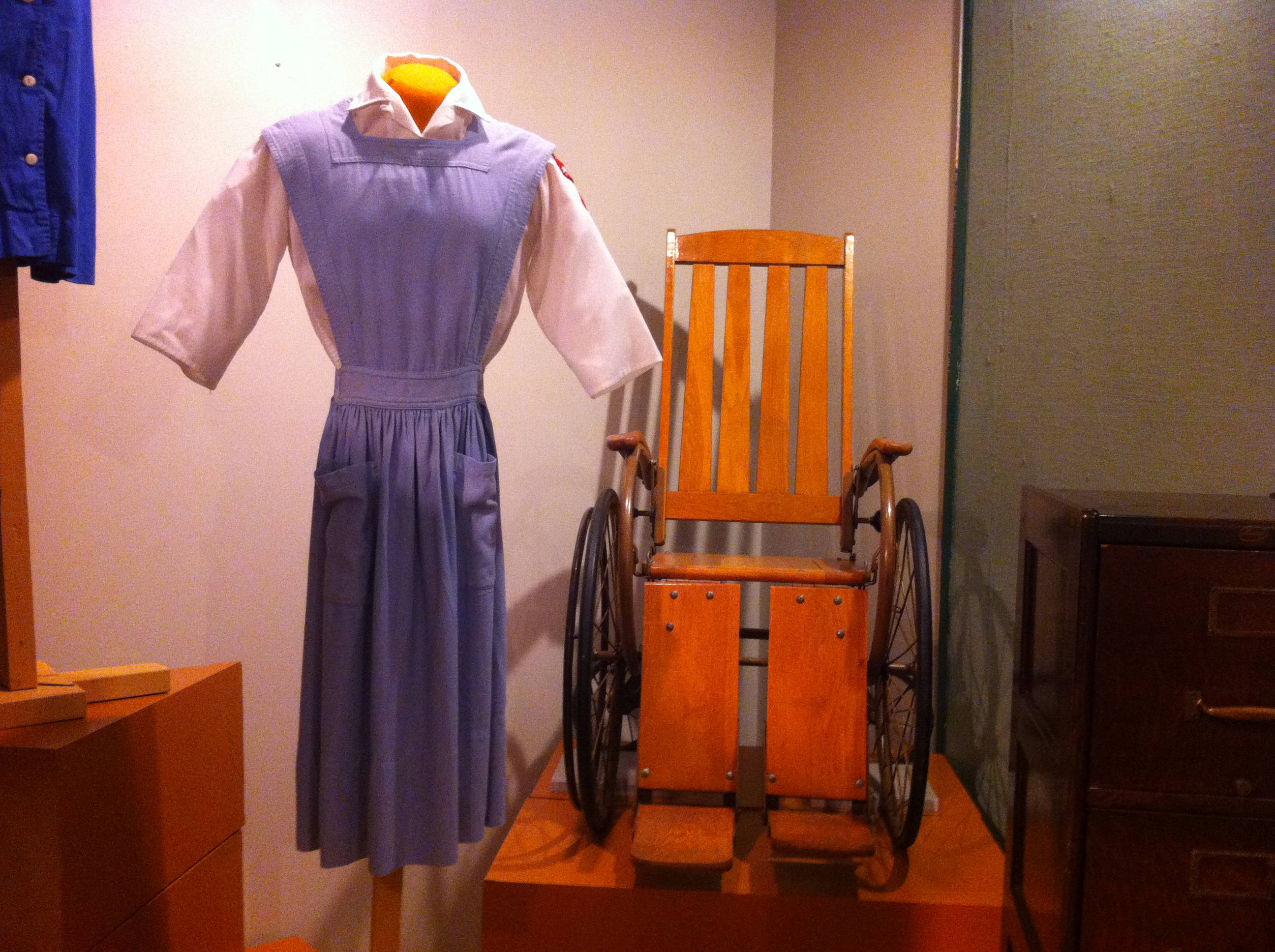 Red Cross Volunteer uniform worn by Jane Jensen at McCune-Brooks Hospital and wooden hospital wheelchair donated to Powers Museum in honor of Dr. Everett Powers when the museum opened. Powers was Chief of Staff when the hospital opened in 1929.