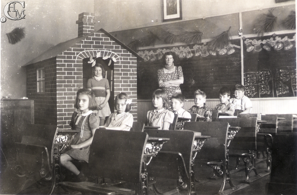 Teacher, Mrs. Brick with students in a classroom from about 1943.