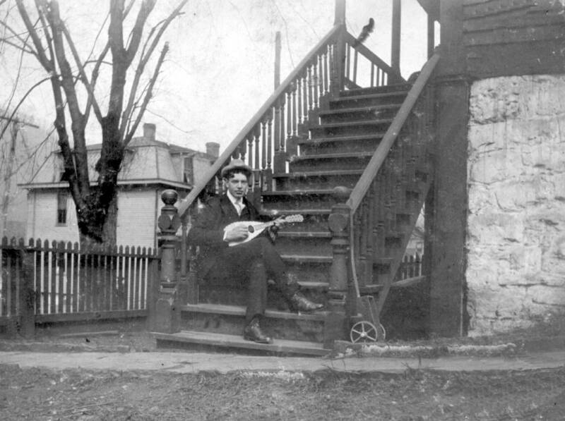 A musician on the steps of the house.