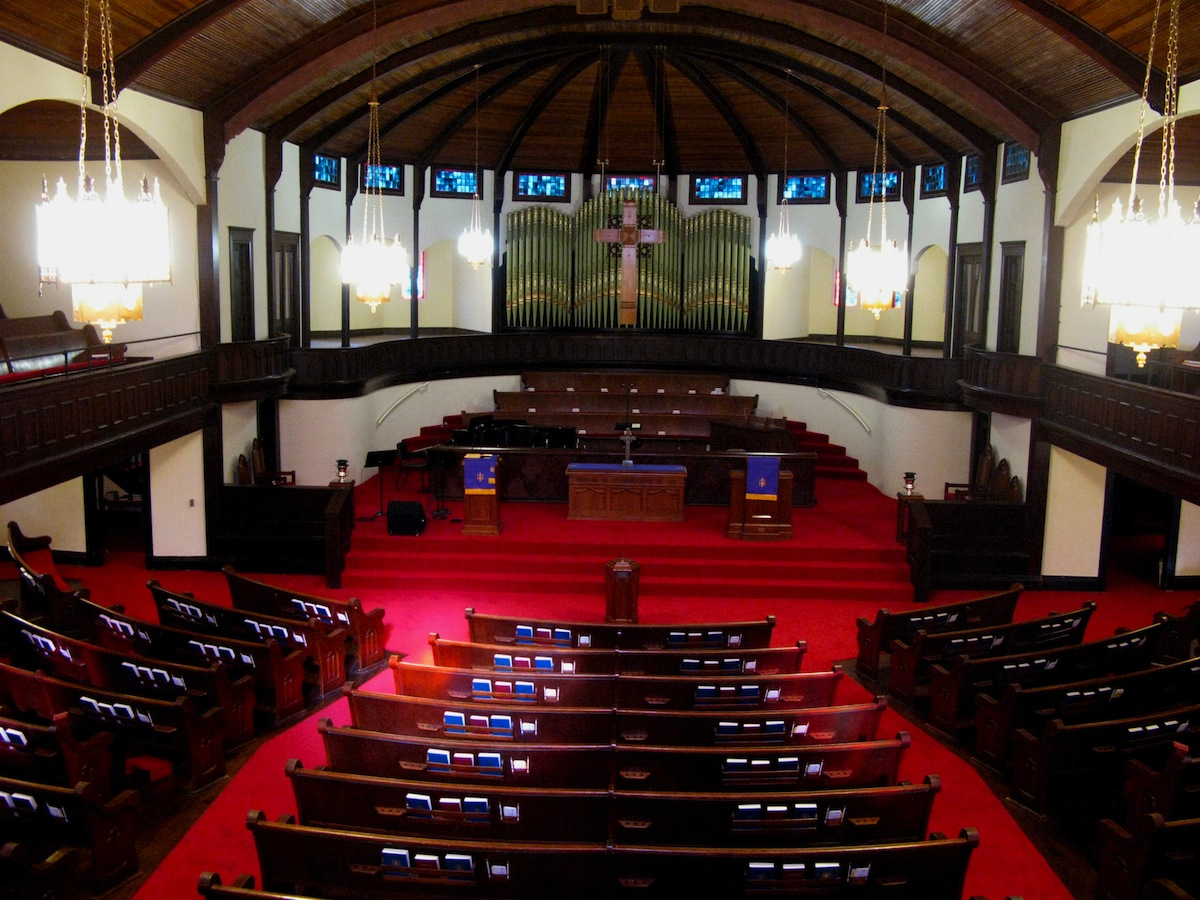 The impressive interior features original pews, an organ, and a beaded board wooden ceiling.