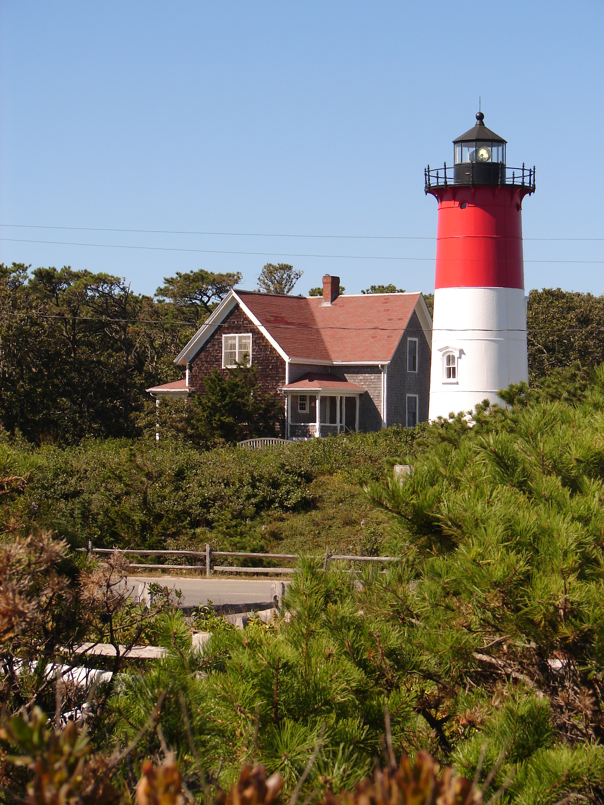 Looking north toward Nauset Light, showing its white light.  The keeper's house (built in 1875 and moved to its current location in 1998) is to the immediate left of the lighthouse.