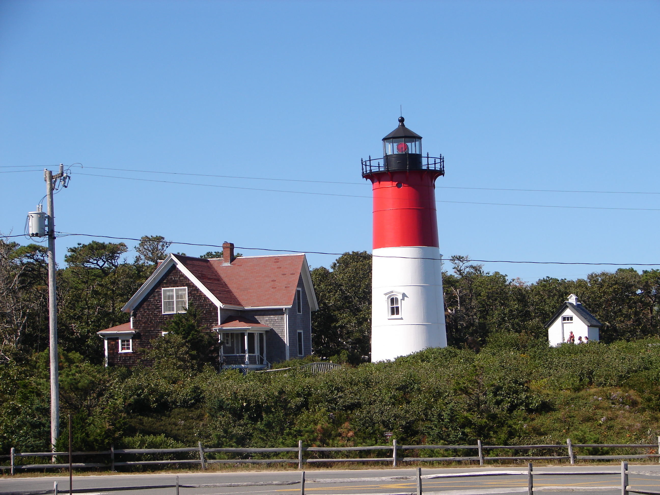 Nauset Light showing its red light (the light alternately flashes red and white every 5 seconds).  The light's oil house (built in 1892, where fuel to illuminate the light was stored prior to the light's electrification) is visible to the right.