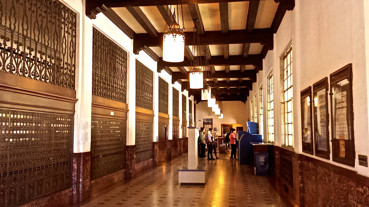 The large lobby of the post office with lantern light fixtures and marble tiled floor.