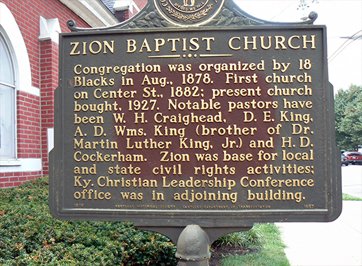 This historical marker is located next to the church