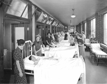 Patients take in the sunlight on the open porches outside of the rooms. (U of L Archives)
