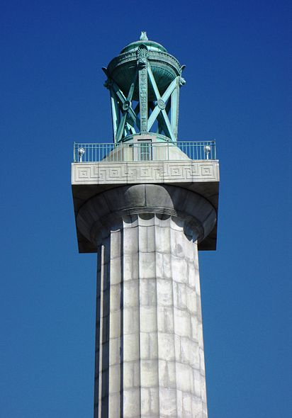 A close-up of the decorative lantern atop the monument