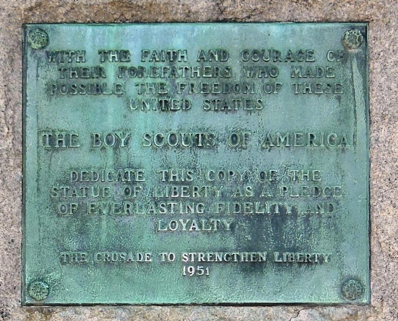 Close-up photograph of the plaque beneath the Statue of Liberty Replica.