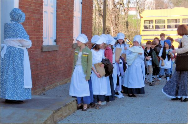 Students entering the school house dressed in period clothing for the day class.