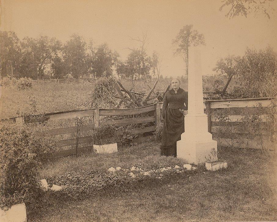Jesse James' mother Zerelda standing at her son's grave