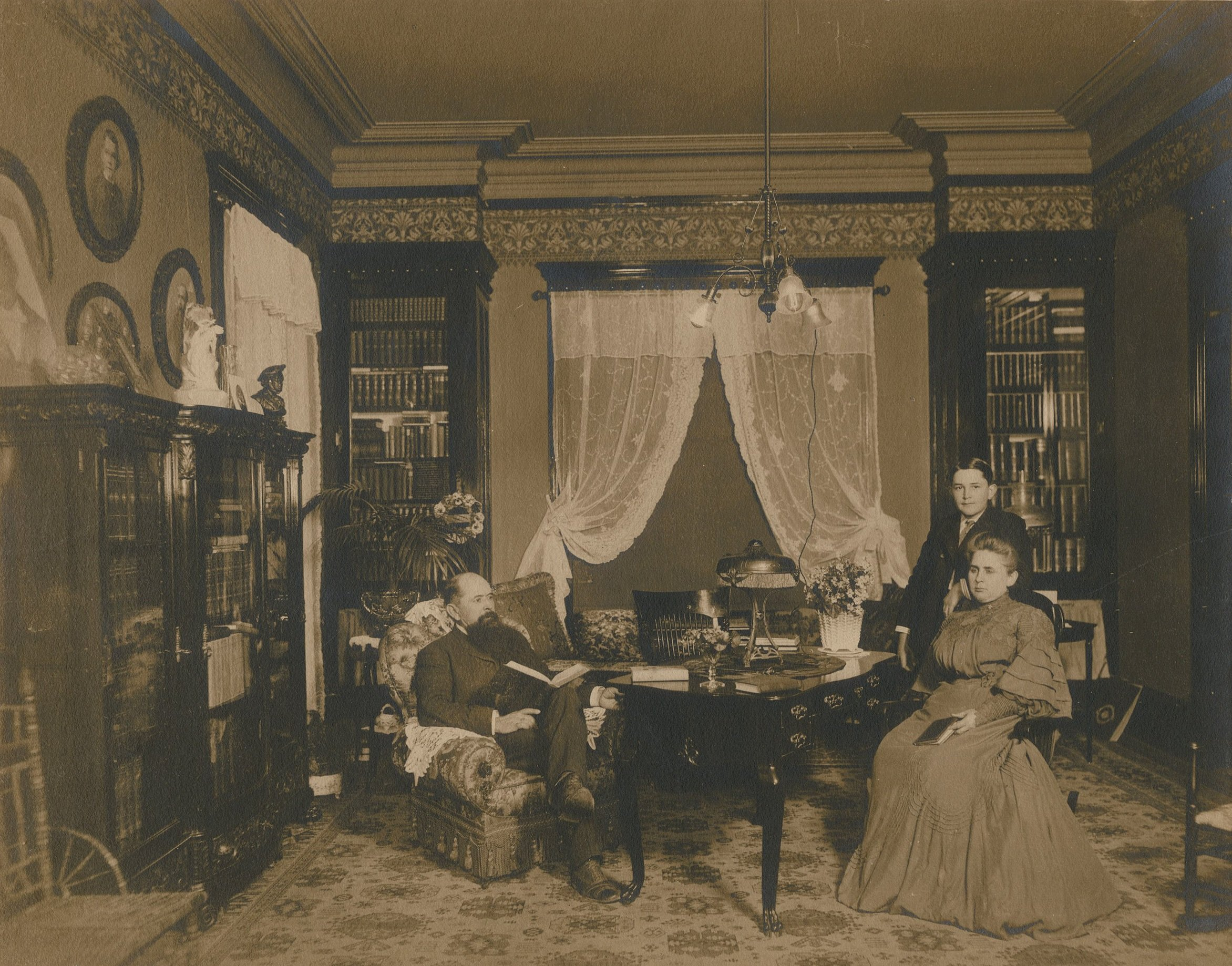 The Stark family, W.H., Miriam, and H.J. Lutcher Stark posing in their library c.1900.