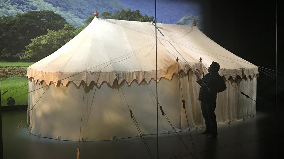 A curator tends to George Washington's original headquarters tent that is part of a larger exhibit within the museum.