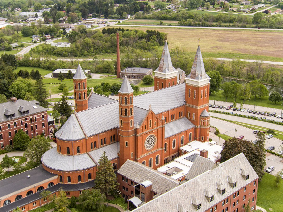 Saint Vincent Basilica has Romanesque Revival design, shown best in the rounded arch windows, and is shaped like a cross.