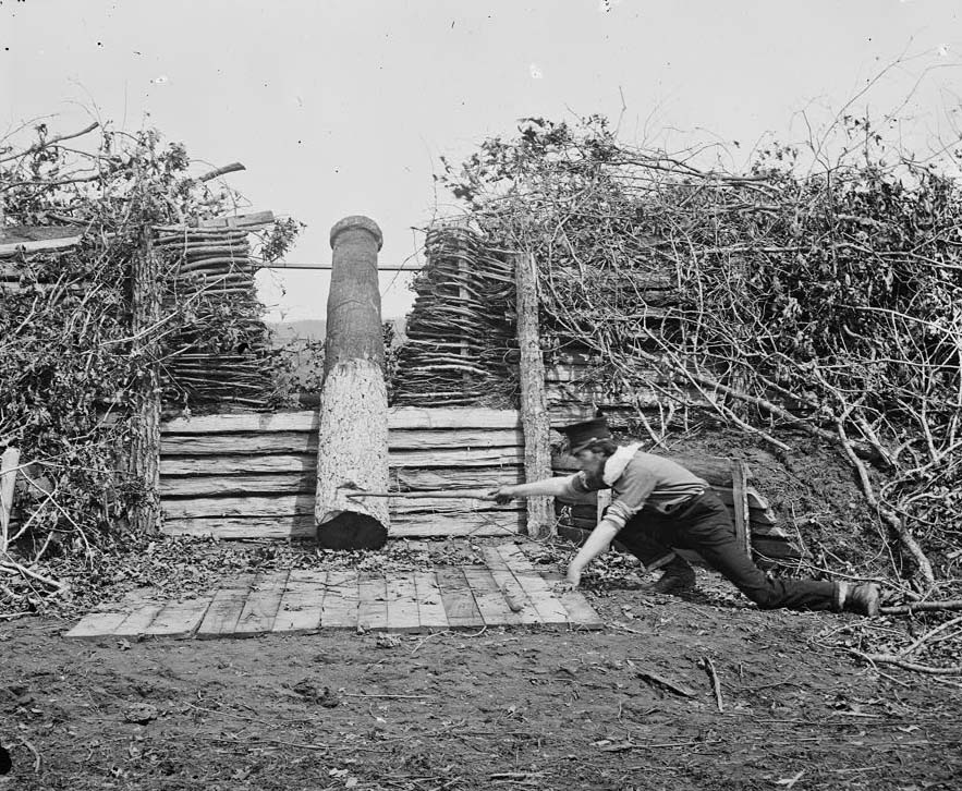 """A """"Quaker gun"""" in Centreville, Virginia, in March 1862; the man in the picture is pretending to """"fire"""" it"""