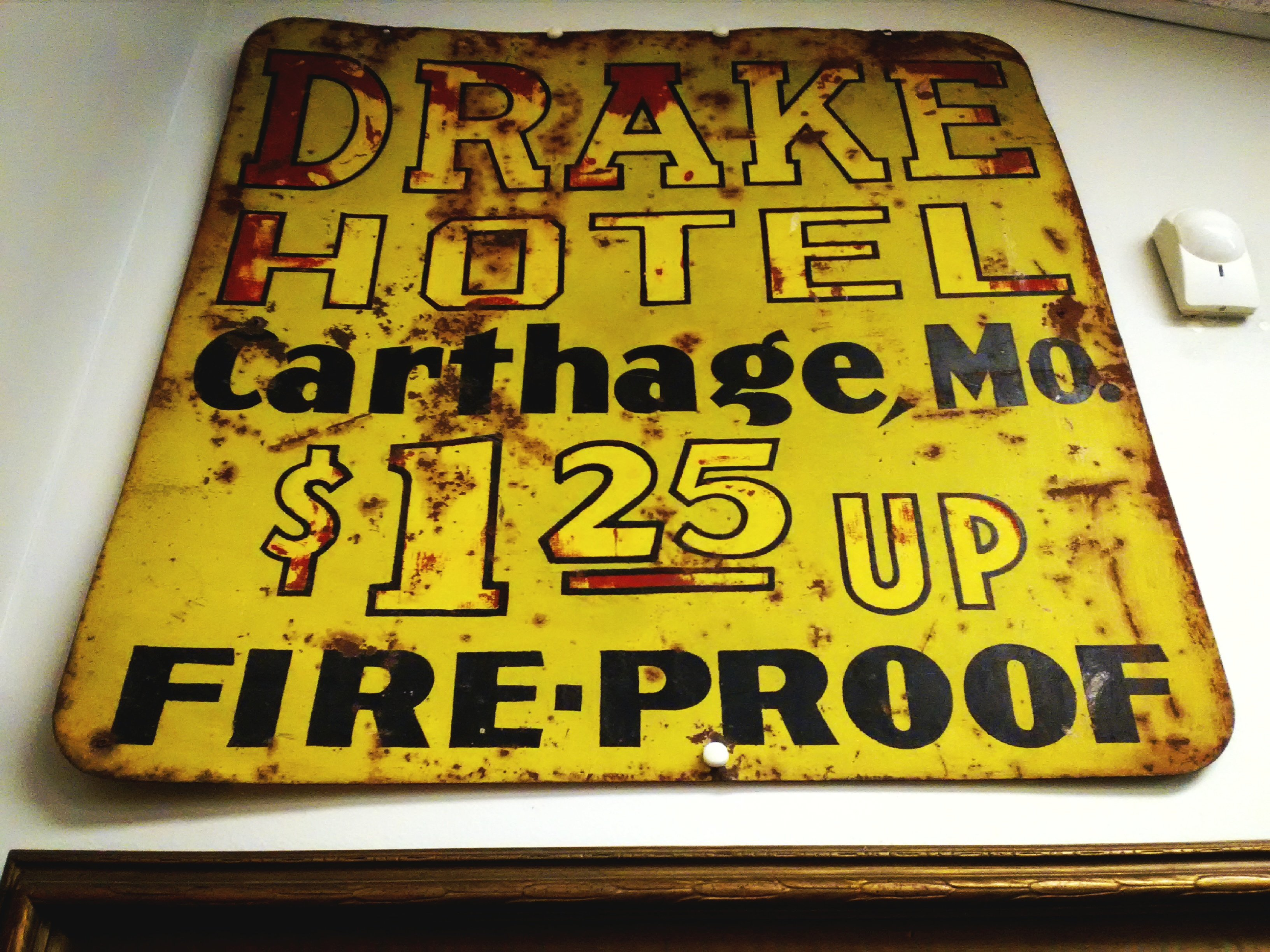 Early metal sign from Drake Hotel on display at the Powers Museum.