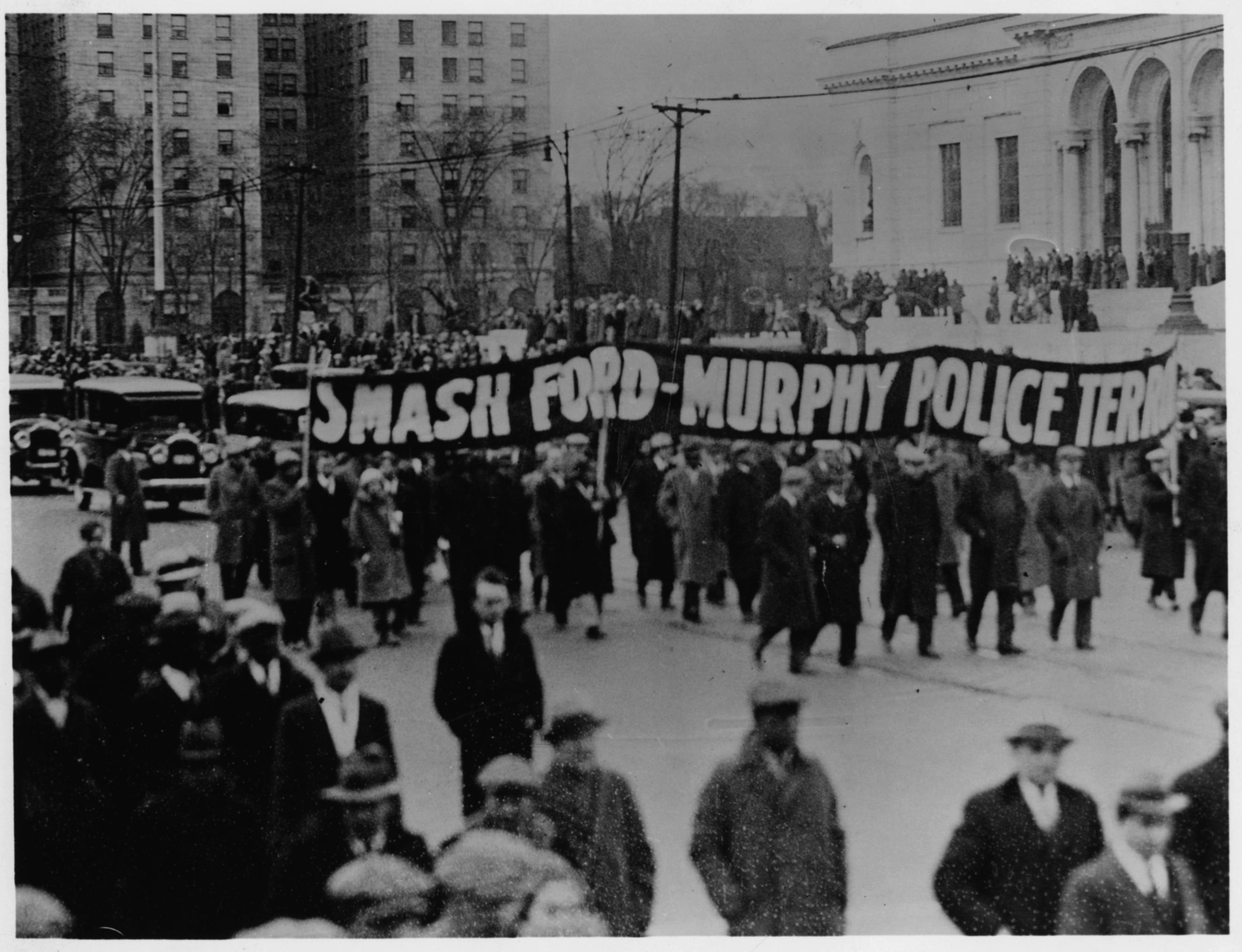"""Banner with the slogan of the funeral march held five days later- """"Smash Ford-Murphy Police Terror"""""""