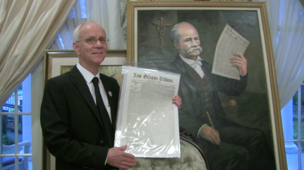 Historian Mark Roudane poses with a portrait of his Great, Great Grandfather, Dr. Louis Roudanez, founder of The New Orleans Tribune, the city's first black daily newspaper.