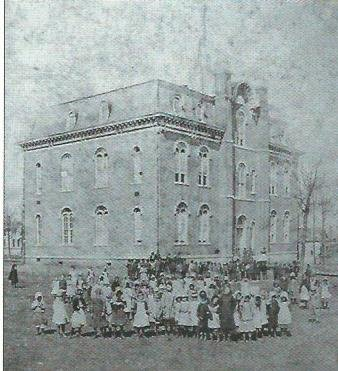 First public school building built after the Civil War. It included all grades up to high school. After construction of a new high school in 1890, this structure became Central School for elementary levels. This image is from an early 1870s stereo view.