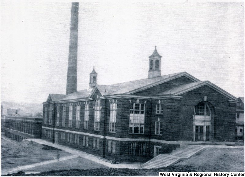 """View of the interior facade of """"shop"""" building featuring the tall smokestack. Date unknown. Courtesy of West Virginia and Regional History Center."""