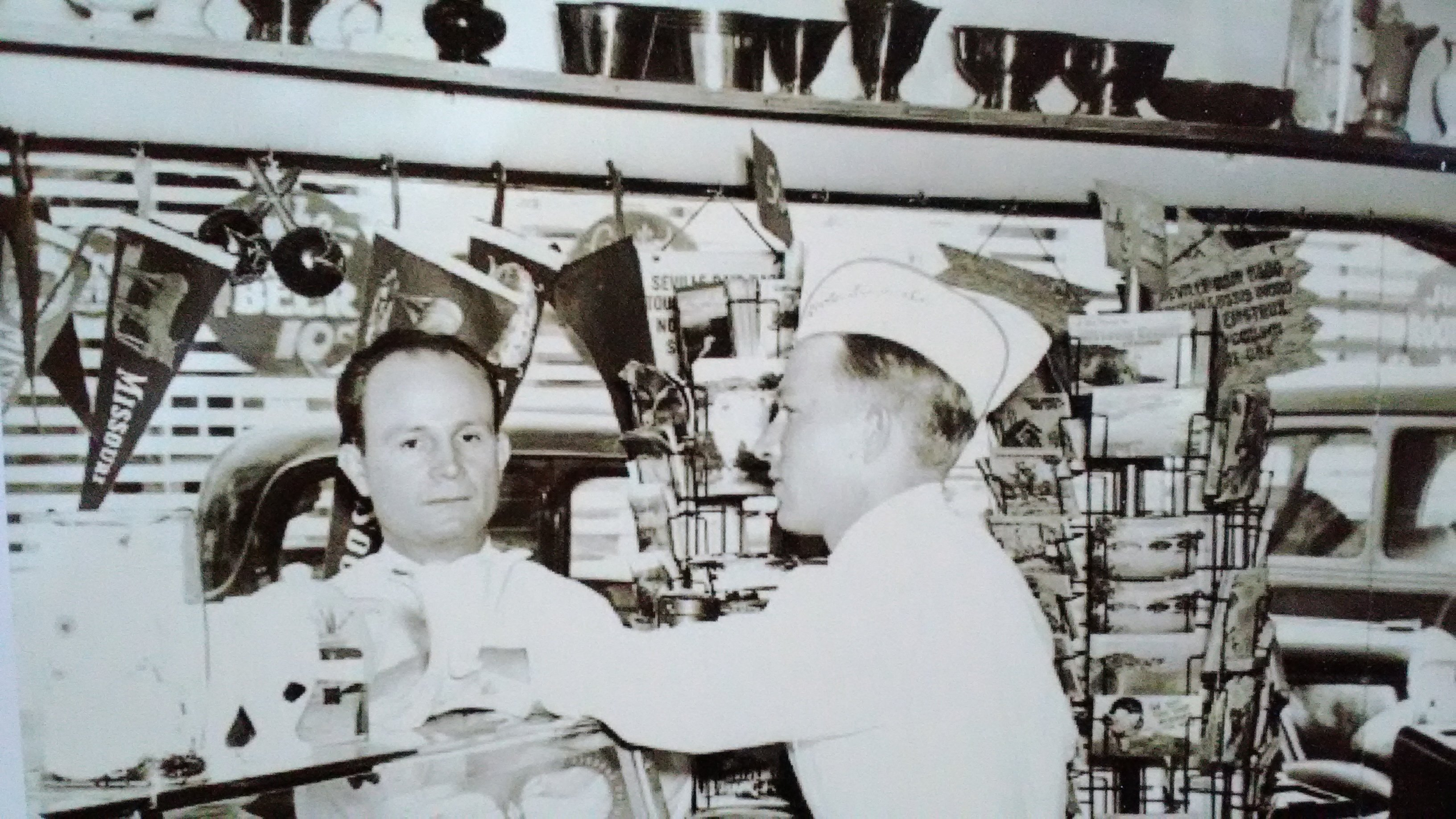 Bob Boots, right, and possibly Lee Crocker, left, at the counter of Boots Drive-In. Boots is standing in front of two postcard racks. Photograph courtesy the late Robert Boots, Powers Museum Collection.