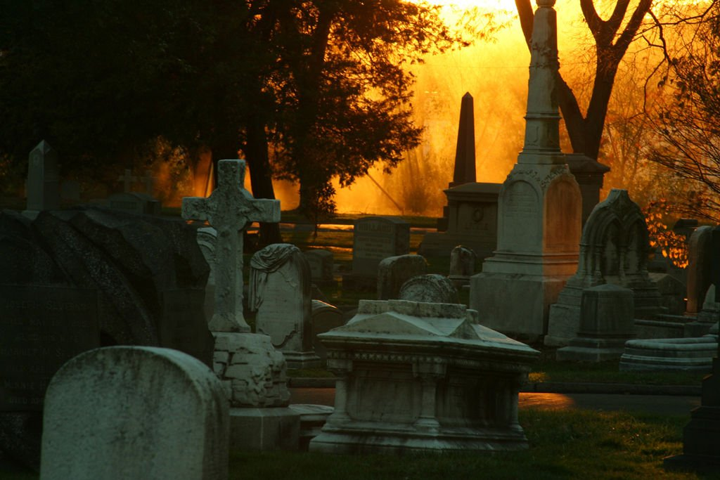 The sun rises on the funerary art at the Woodlands cemetery.
