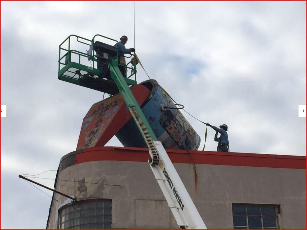 Removing the beloved paint can from the roof of Evans Lumber in 2015. The can is now in the possession of the City of South Charleston.
