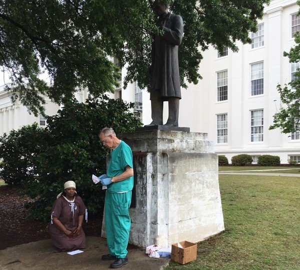 Two protesters portray Dr. Sims performing an operation on an enslaved woman. The physician was arrested by capitol police. Photo from Al.com report which is linked and cited below.
