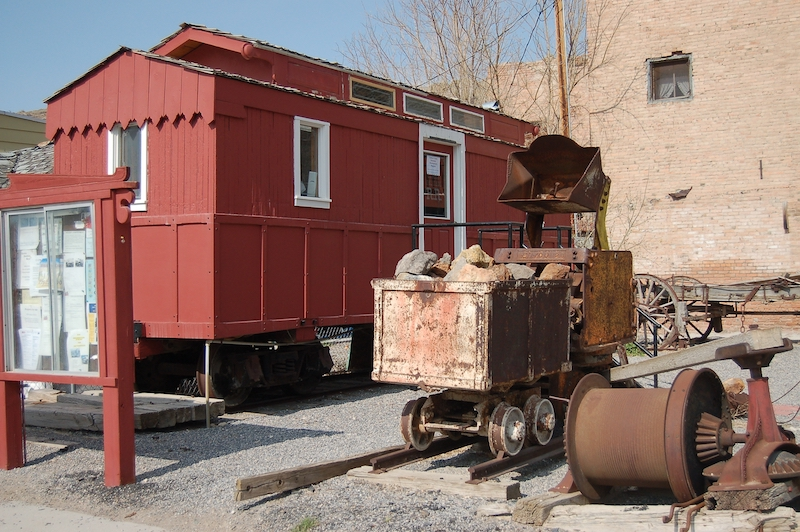 The Eureka and Palisade Railroad car is on display next to historic mining equipment.