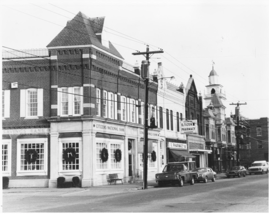 North Side of Main Street incl. Charles E. Tilton Block, Bank Block, Alfred Tilton Block, and the Side of Tilton Block.  Steeple of Northfield-Tilton Congregational Church visible above Alfred Tilton Block by Roger P. Akeley on December 15, 1982