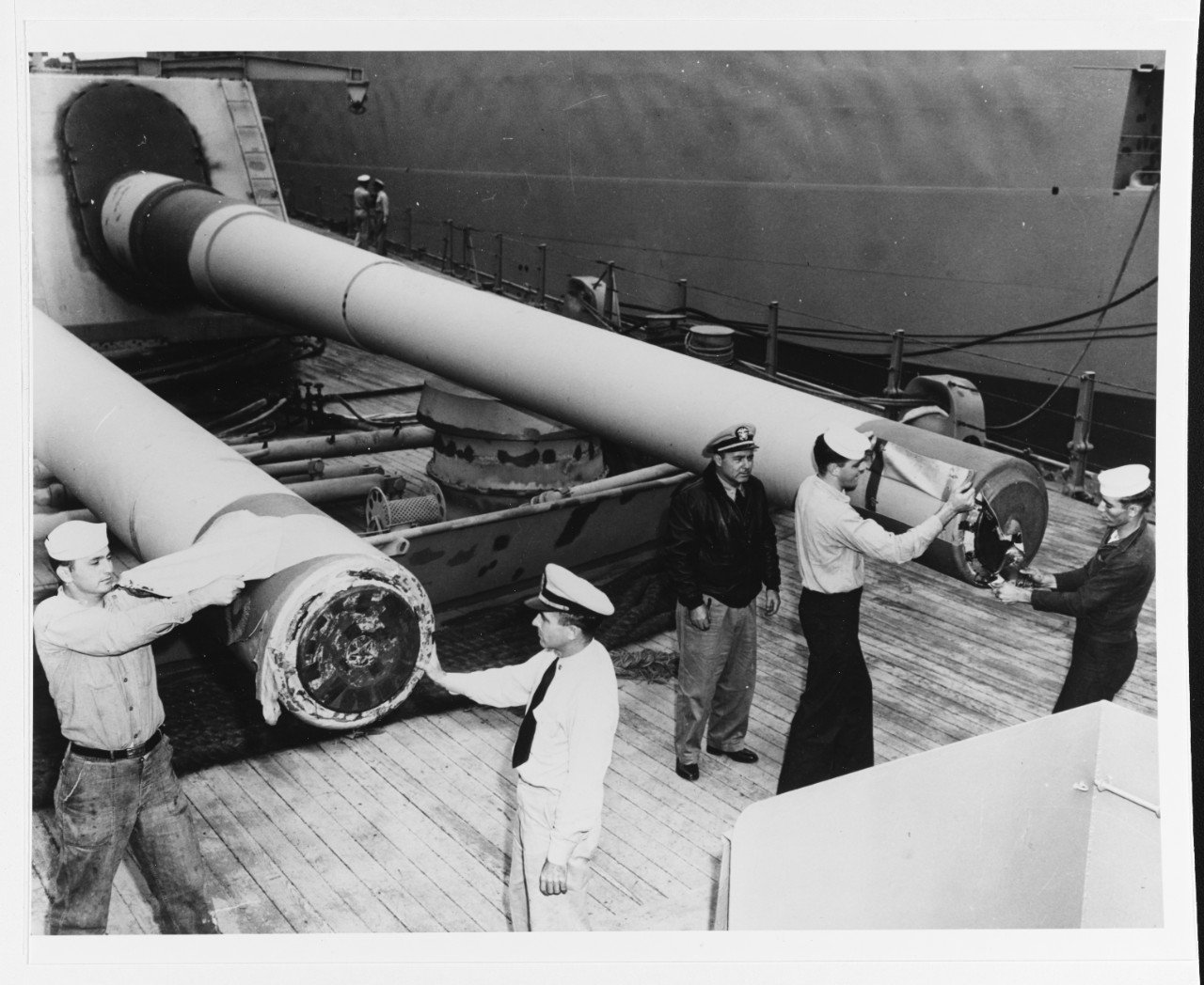 "New Jersey's crew remove muzzle seals from the forward 16"" guns during her 1950 reactivation. (NHHC)"