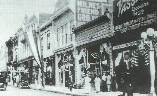 Milnes-Friend grocery occupies 110 East Fourth in this photograph, c.1915. Also visible in this image are the buildings at 100 and 106 East Fourth Street.