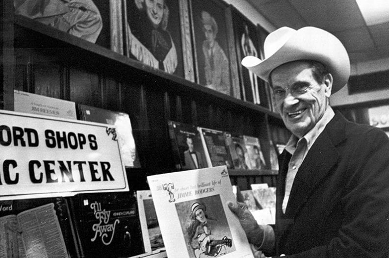 Ernest Tubb Holding a Jimmie Rodgers Album in the Ernest Tubb Record Shop, January 9, 1978