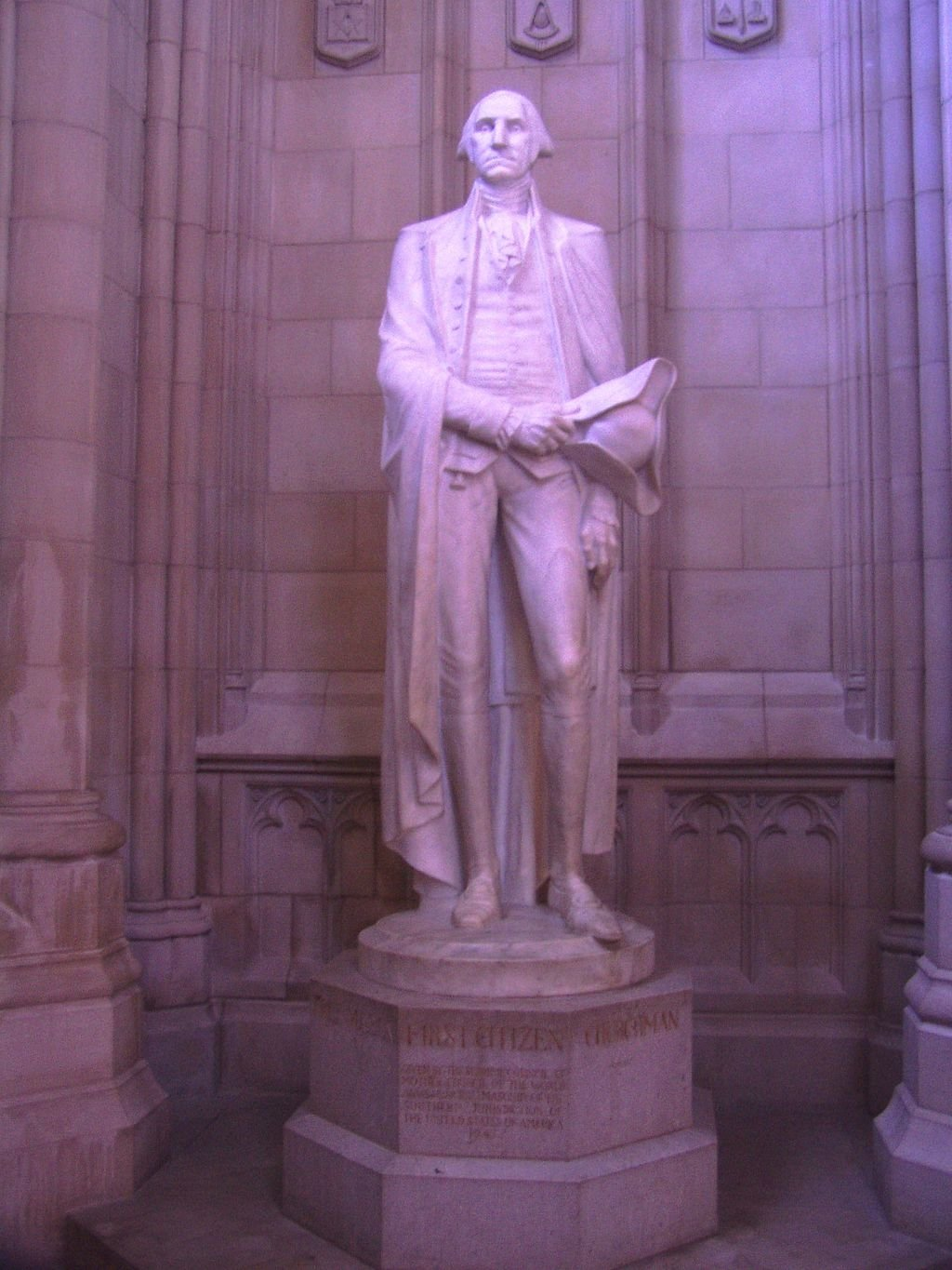 A statue of President George Washington, who planned the Cathedral, stands in an alcove where symbols such as his coat of arms can be found. Photo by Danvera, English Wikimedia.