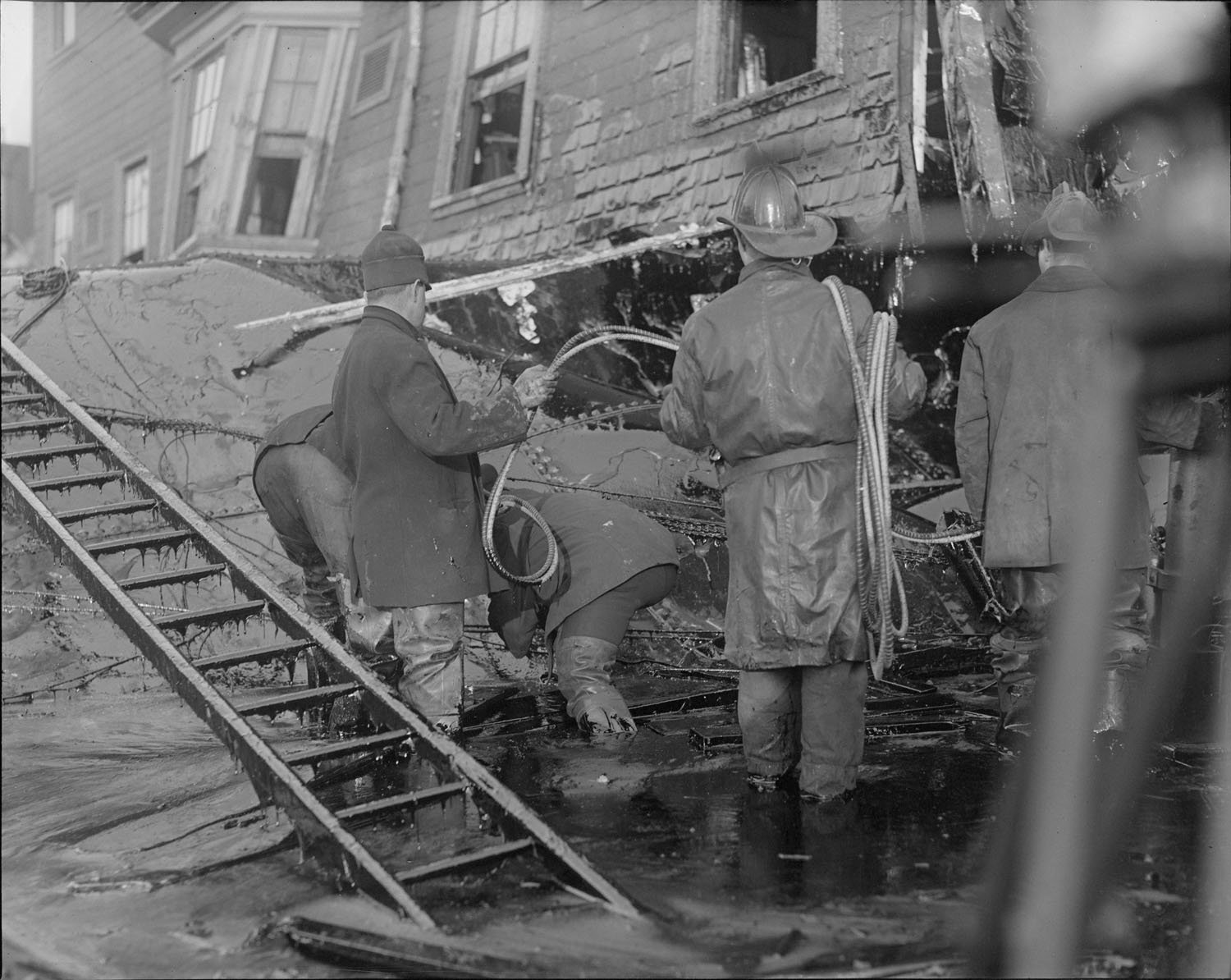 Firemen standing in knee-deep molasses while searching for survivors. 