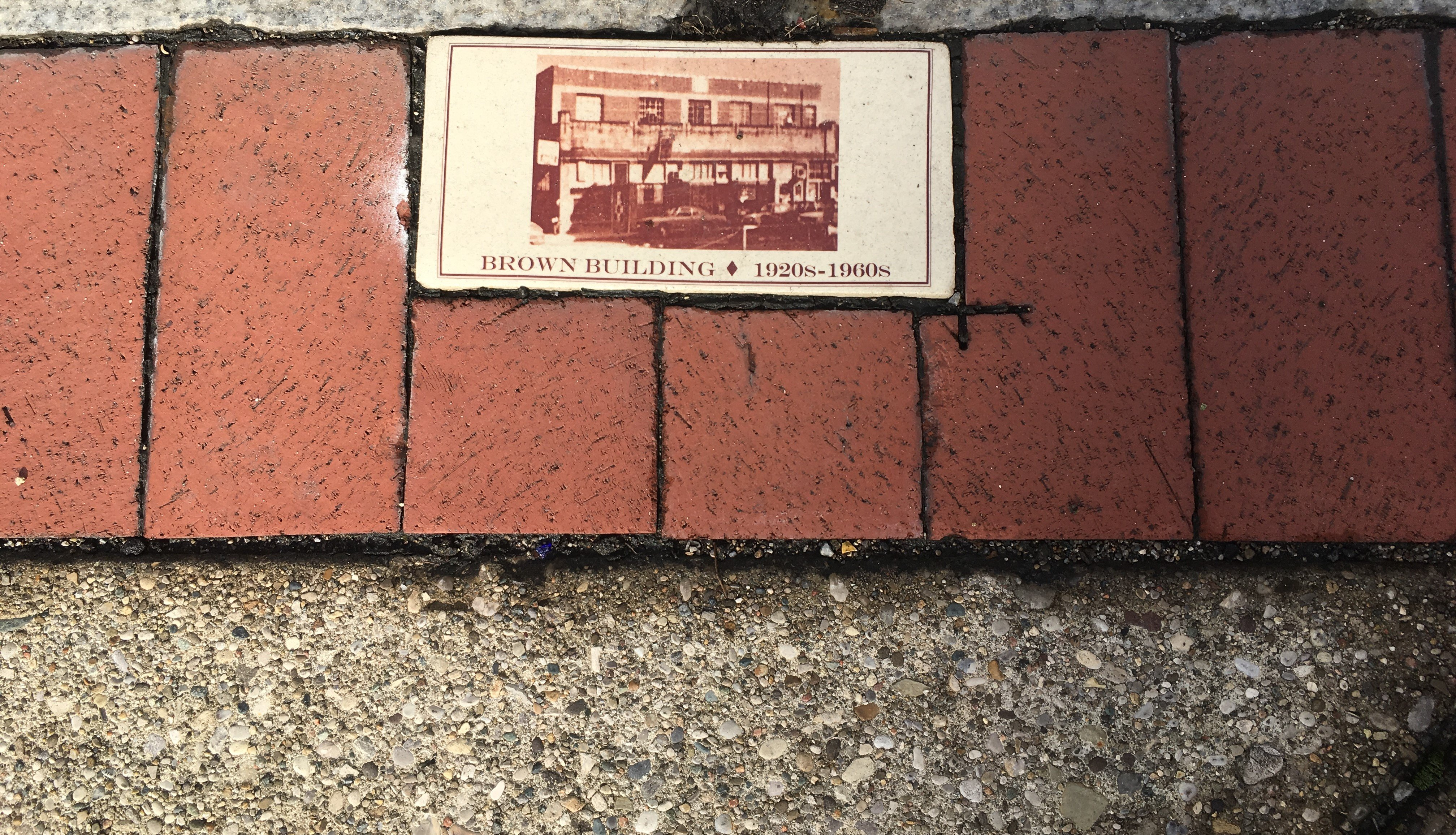 "A historical brick placed by the West Virginia Center for African American Art & Culture;  marking the corner of Washington Street, East & Shrewsbury Street on ""The Block"";  original site of Anderson H. Brown Building, 1920-1960."