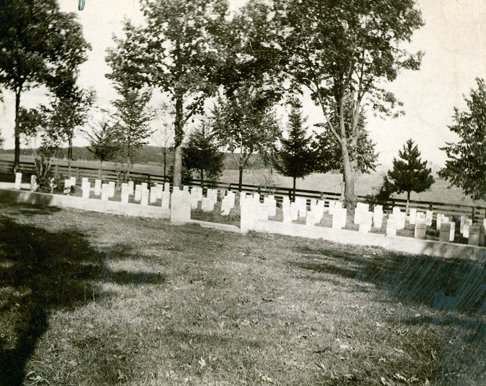 Photograph of Confederate Rest, Forest Hill Cemetery, Madison, Wisconsin. Featured is the stone fence around the graves, the grave markers and a memorial stone with the names of all of those buried there, including Alice Whiting Waterman.