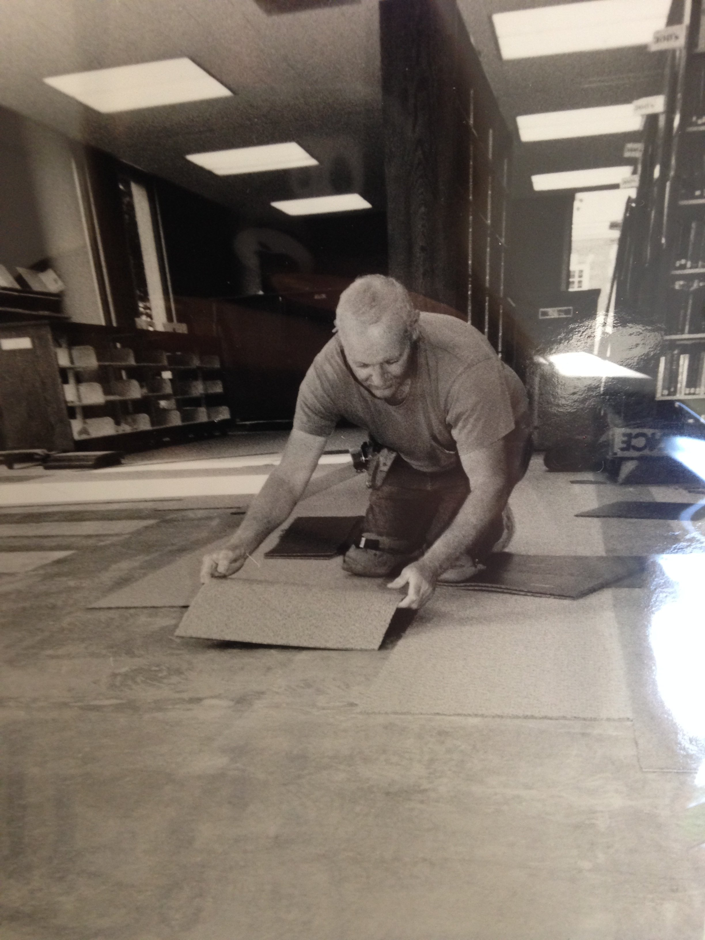 This is a photograph of a worker laying the carpet during the construction of Schewe Library.
