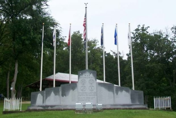 The full granite memorial with the United States flag and the Army, Navy, Marines, and Air Force flags.