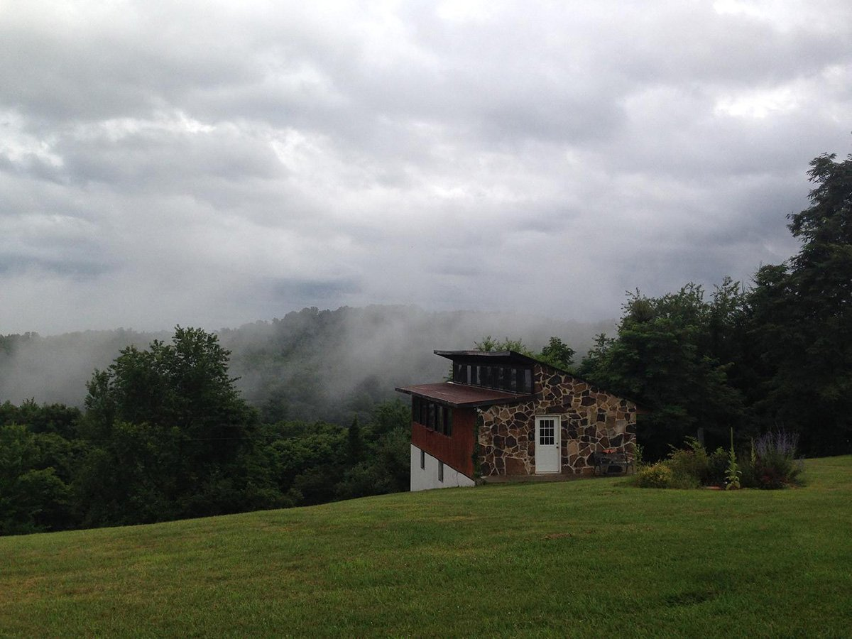 a church type building overlooking a valley in the mountains.