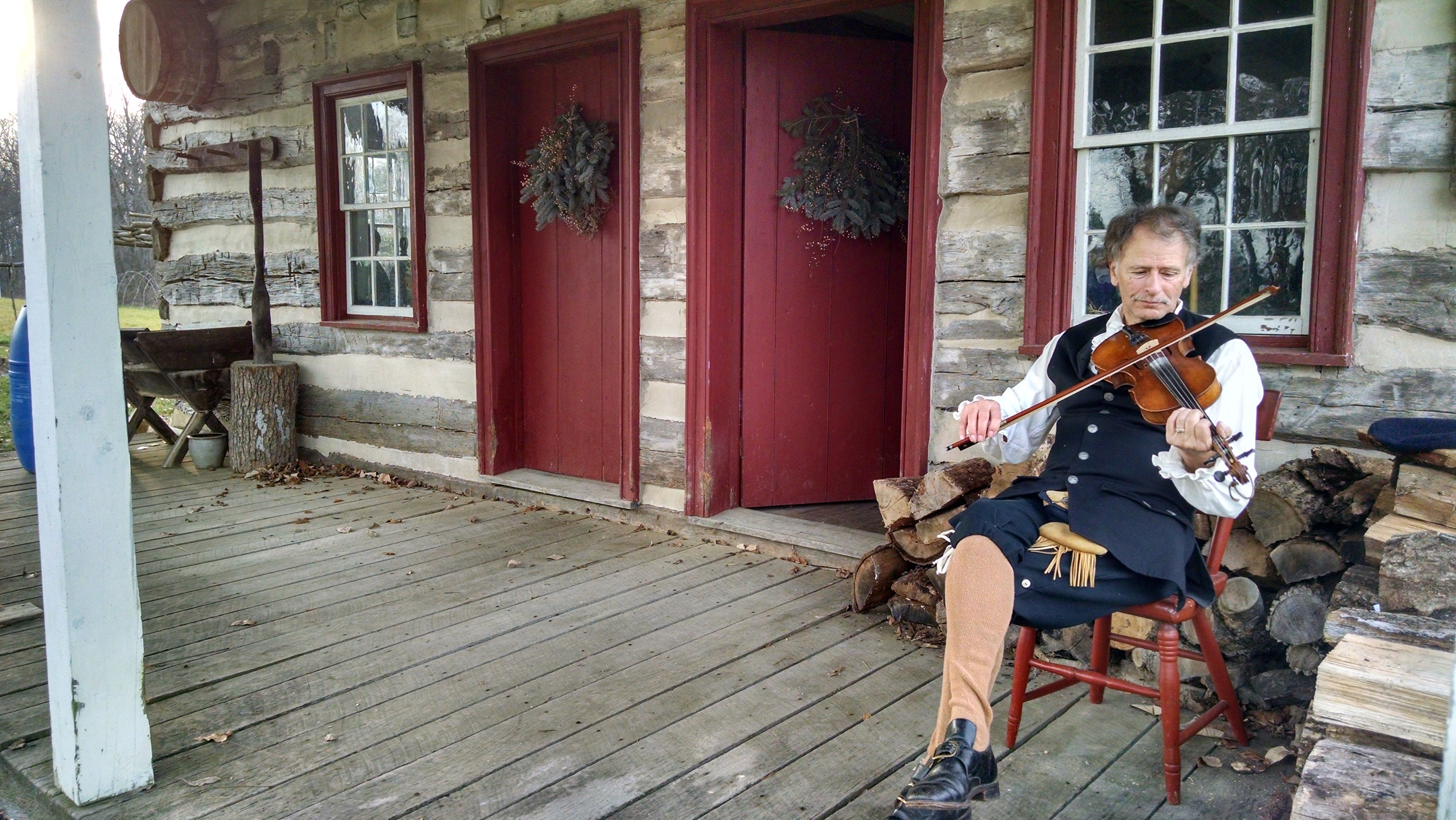 A fiddler enjoys unseasonably warm weather during a Christmas Open House. Annual event the second Saturday of December. Come see the Conococheague Settlement dressed in period decorations.
