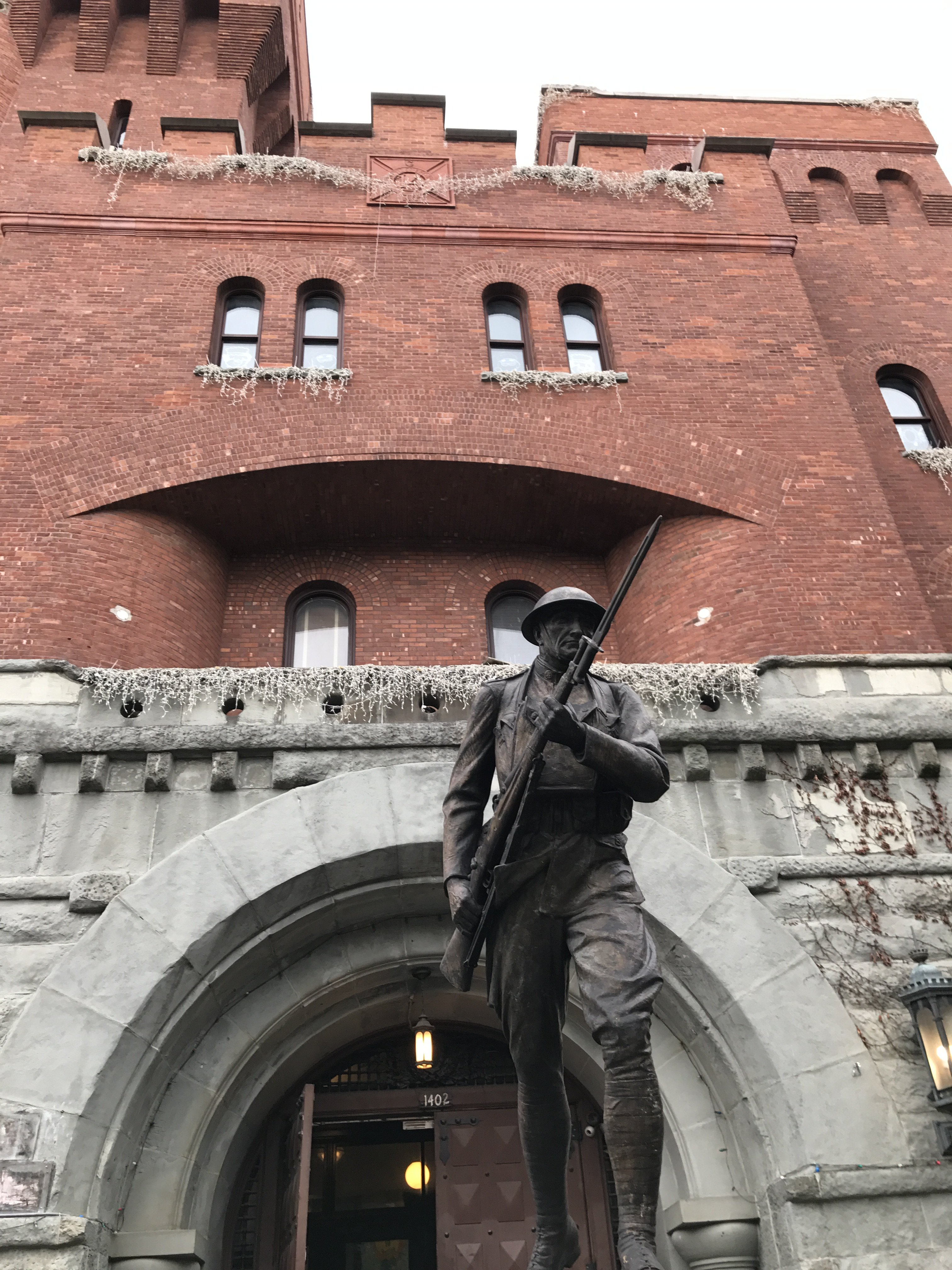 Another front shot of statue, with exterior of building behind the statue. The building behind is the original armory building which has been converted into a community space, museum and YMCA