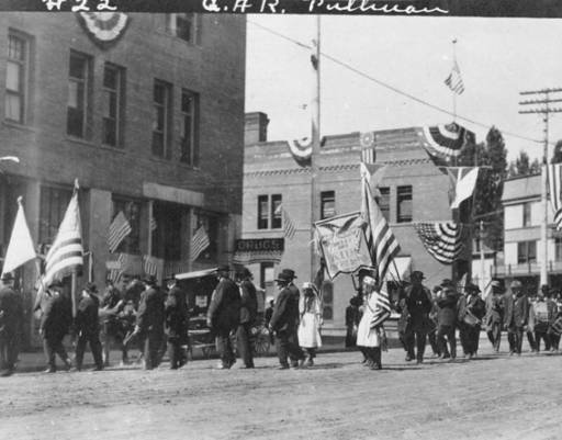 A parade procession heading down Main Street with the Artesian Hotel and the Flatiron Building (middle) in the background. Taken by Artopho Studios in 1912. Courtesy WSU Special Collections.  http://content.libraries.wsu.edu/cdm/singleitem/collection/pul