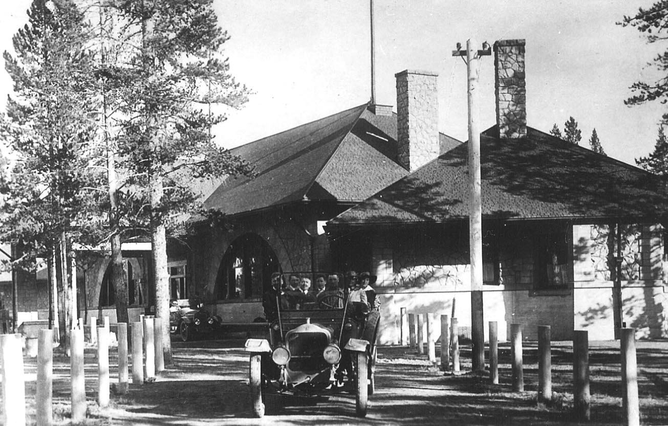 Historic photo of the depot with passengers all loaded up ready to tour Yellowstone National Park. This photo shows the west wing.
