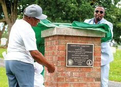 Individuals unveiling a plaque at the historic African American cemetery, Newtown, in Harrisburg, VA.