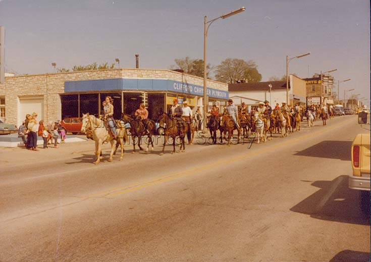 Clifford Chrysler Plymouth, 325 N. Milwaukee Ave., during Bicentennial Wagon Train Parade, 1976
