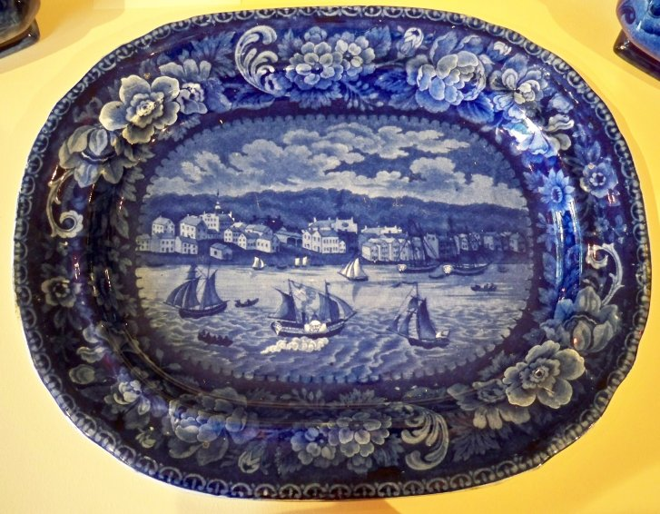 "Historical Blue Platter English, mid 19th century. In the ""Sandusky"" pattern with ship ""Henry Clay"" in the harbor. Scratches and the table wear to the back. Monor roughness on the rim.  The small building at the extreme east was the first building where ice cream was sold in the city. Next to the north was Doll's Hotel with a dance hall in the upper story. The building with a spire was the Episcopal church for which the cornerstone was laid in 1835 and Wm. T. West and his wife were the first couple married in the church in 1844. Between the church and Doll's Hotel was Charles Rice's wagon shop. The large building with the sheds was the Steamboat Hotel, later called the Verandah, at the foot of Wayne Street, which was raised in 1923. East of it was a boarding house kept by the Widow Hurd. To the southwest of the Steamboat Hotel was the first stone house in Sandusky, built by Eleutheros Cooke, where the Star Theatre now stands. The building west of the Cooke residence are the Methodist and Congregational churches. West of the Steamboat Hotel on Water Street was William Boos' Bakery. then came a boarding house. Then to the west, the residence of Captain Ransome and the larger four story building was the Ohio House. The third building from the westside of the picture was William Townsend's store. The rest of the buildings were mostly log cabins. The Henry Clay was built in 1838. The picture does not show Colt's Exchange Hotel, which shows the picture was prior to April 1842, when Charles Dickens visited the city."