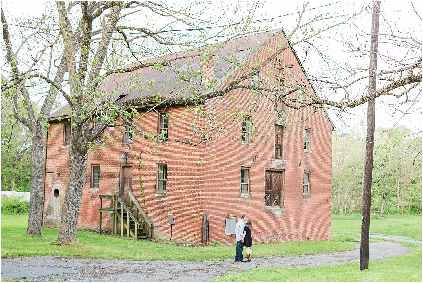 A happy couple celebrates their engagement in front of the grist mill.