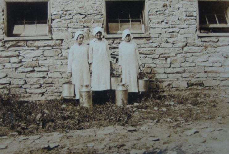 Milk maids in front of the Apple Barn when it was used as a the first dairy barn.