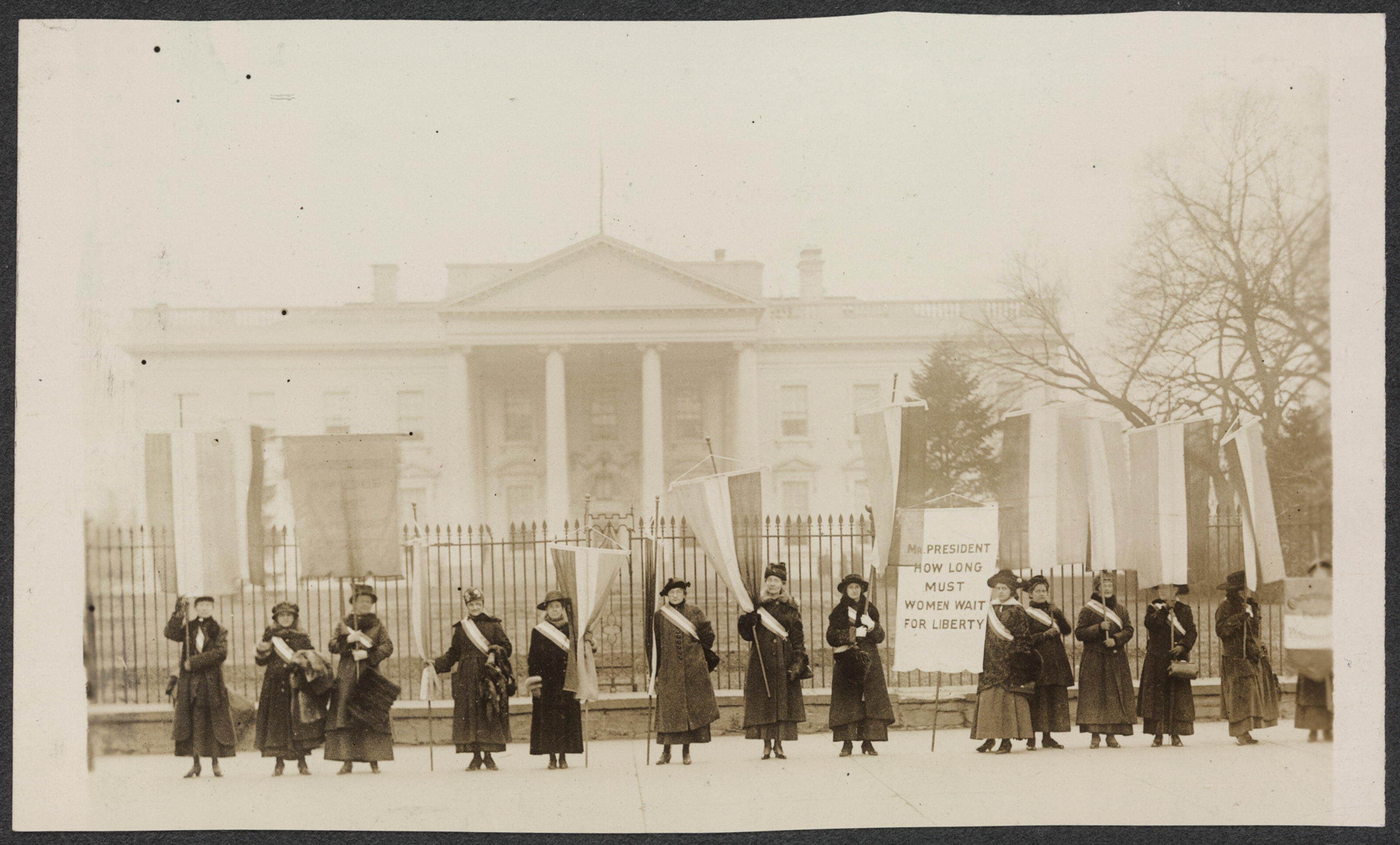 Members of the National Woman's Party stand in front of the White House to make a statement for women's suffrage. Library of Congress.